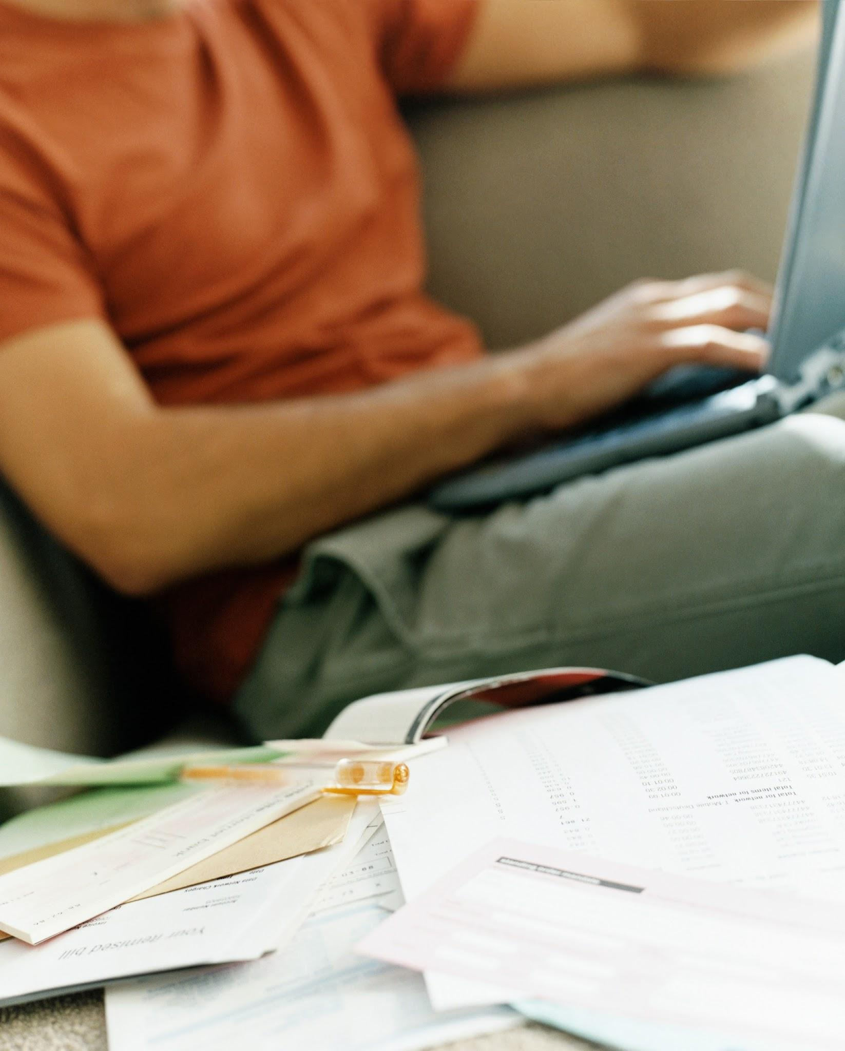 Pile of Invoices, Man Using Laptop on the Background